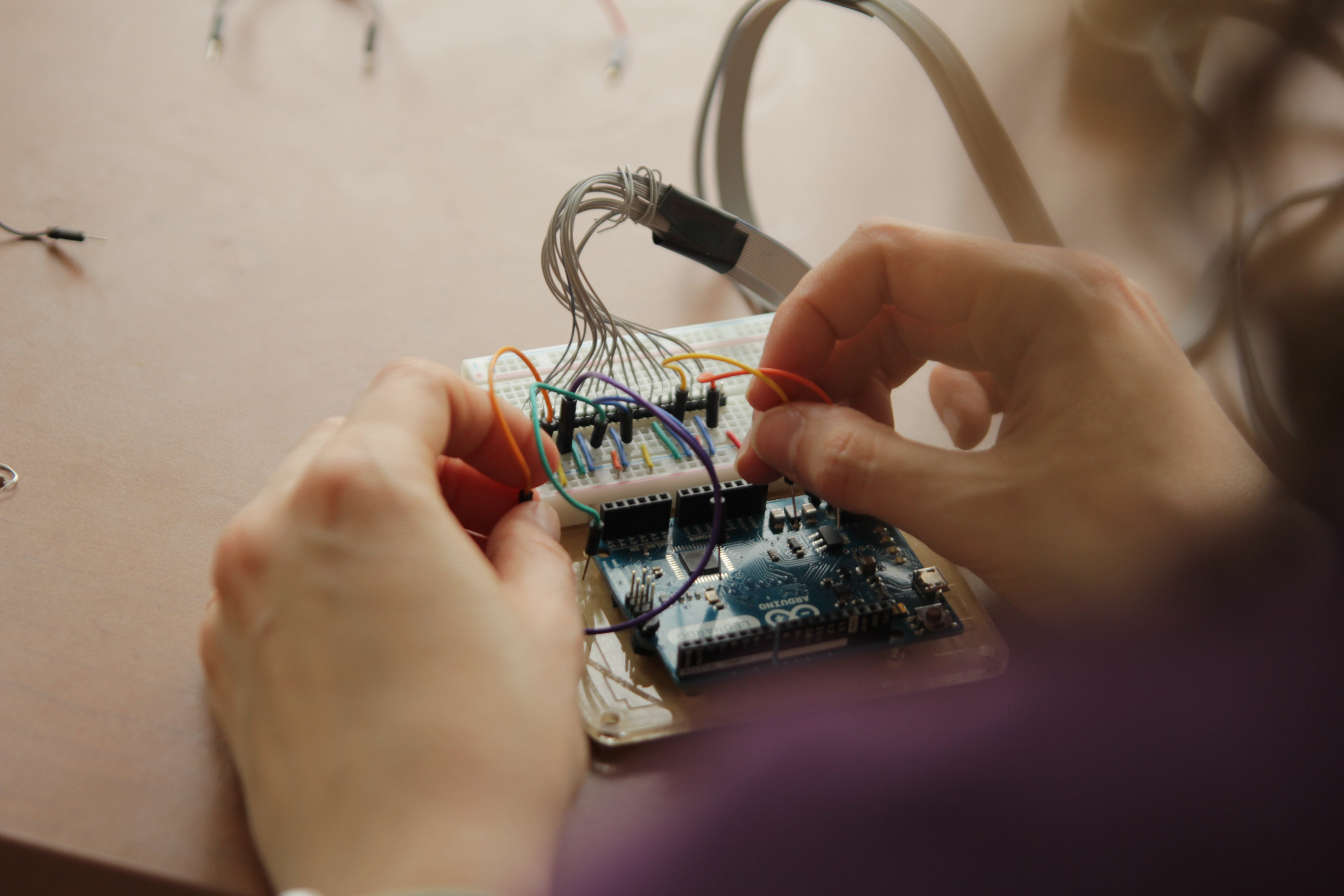 Picture showing and Arduino microcontroller, where wires are being connected by the researcher